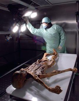 A researcher stands over the body of Ötzi the Iceman, a 5,000-year-old mummy found on the mountainous border of Austria and Italy