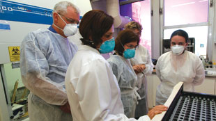 In Brazil, Ann Ginsberg (center) consults with a TB drug-research team.