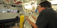 Todd Olin, a pulmonary fellow in Robert Roach's lab, works the cycle ergometer in the hypobaric chamber while breathing a special gas mixture that is high in CO2. Roach wants to test Olin's ability to hold CO2 levels constant.
