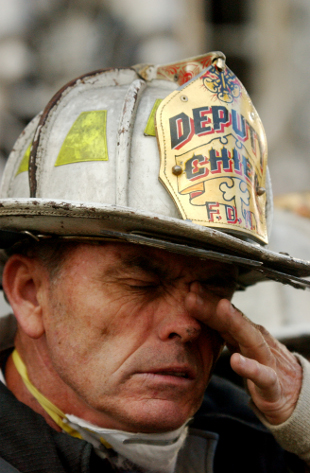 A firefighter clears soot from his eyes