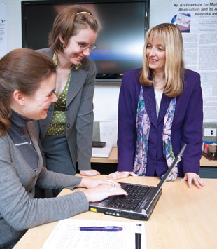 Carolyn McGregor (right) in her Health Informatics Laboratory at the University of Ontario Institute of Technology consulting with other researchers about Artemis, a software program that stores long-term data on neonate physiology, and looks for overarching health trends.