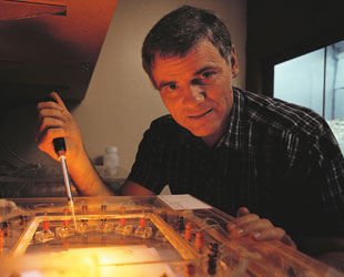 Leroy Hood poses with the original automated DNA sequencer he codeveloped, the prototype design for which was published in June 1986.
