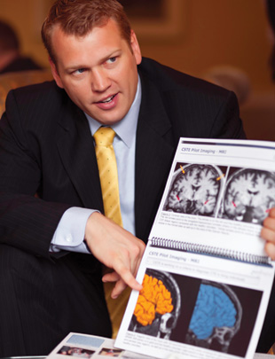 Nowinski pointing to scan of a 50-year-old former NFL player's brain (yellow) next to a control (blue).