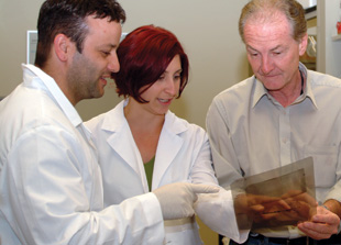 LOOKING AT FAT: Eric Ravussin (right) of Pennington Biomedical Research Center in Baton Rouge, Louisiana, and two of his mentees, Madlyn Frisard and Anthony Civitarese, read a Western blot to look at proteins important in the development of brown adipose tissue.
