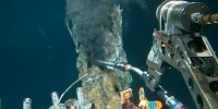 A mechanical arm on the Alvin submersible reaches out to take a sample from a